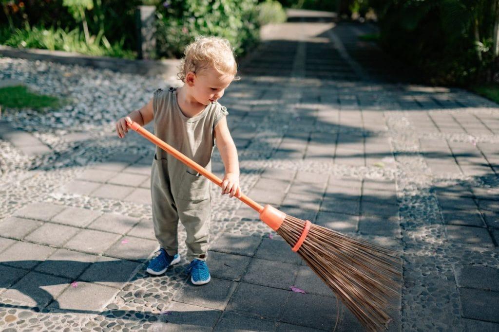 Kind bezemt tegels buiten