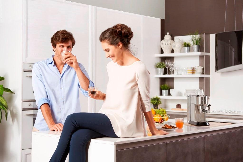 Man en vrouw drinken koffie in de keuken
