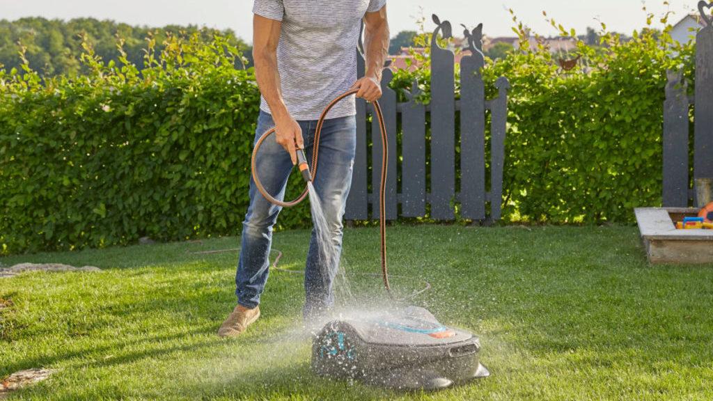Iemand die de robotmaaier schoon maakt met de tuinslang