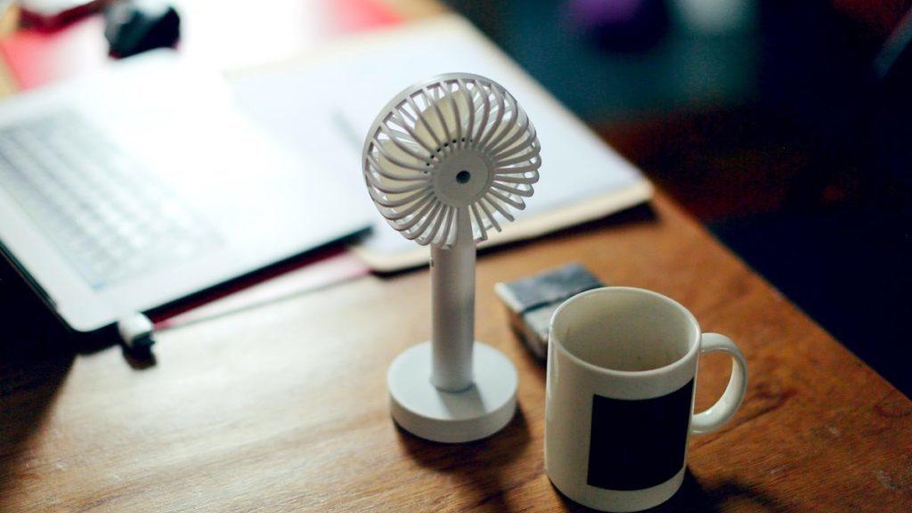 Kleine ventilator bij mok op de tafel