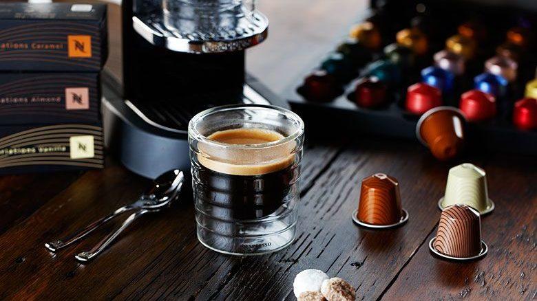 Nespresso apparaat met glas koffie en cups