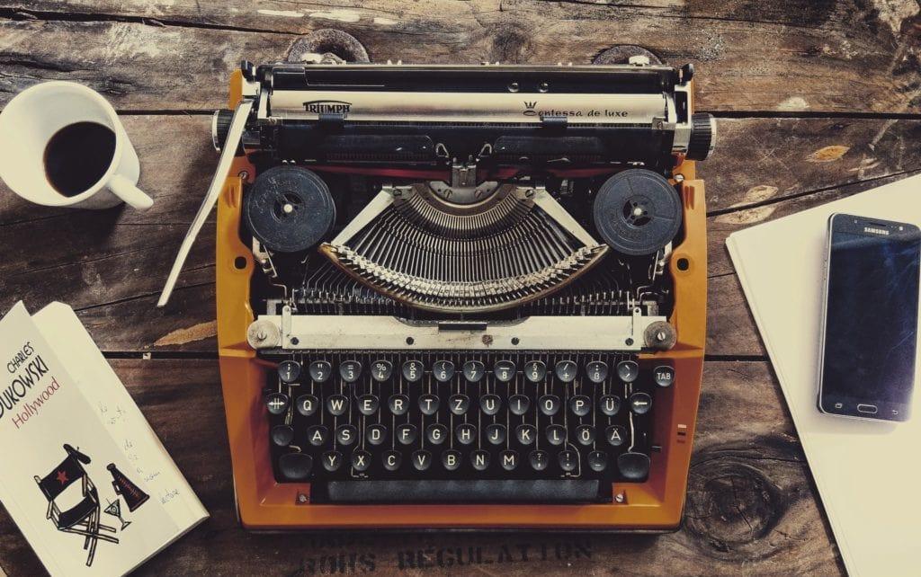 Oude typmachine op een houten tafel met koffie en smartphone ernaast