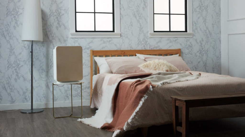 Slaapkamer met bed en luchtreiniger op tafeltje