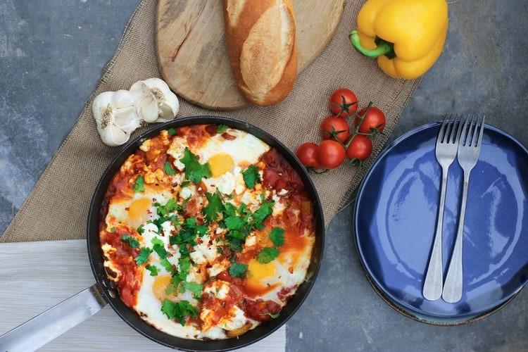 Koekenpan bovenaanzicht met ei en tomaat erin
