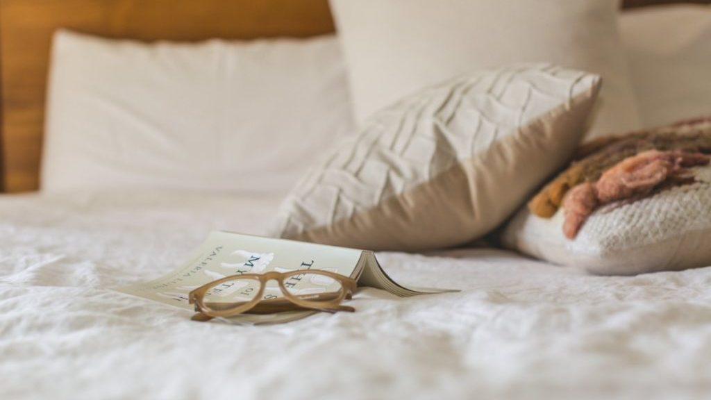 bril en boek op dekbed