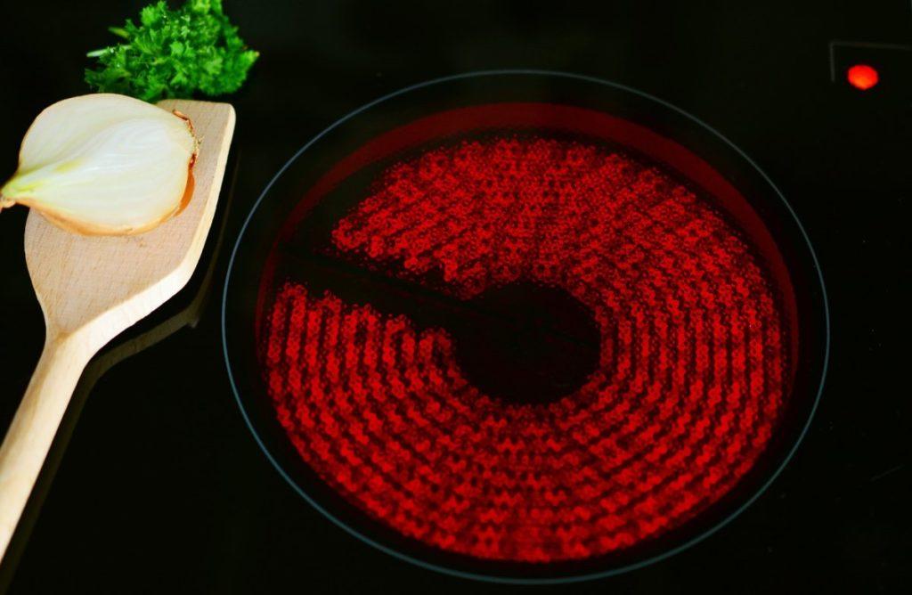 Elektrische kookplaat aan met ui op een houten lepel