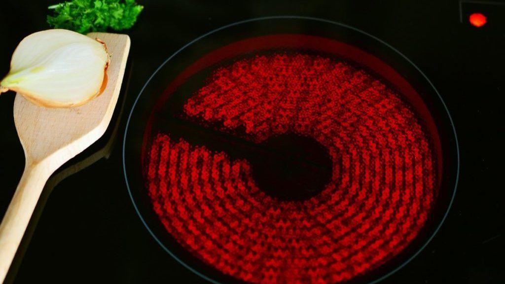 Keramische kookplaat met houten lepel ernaast, bovenaanzicht