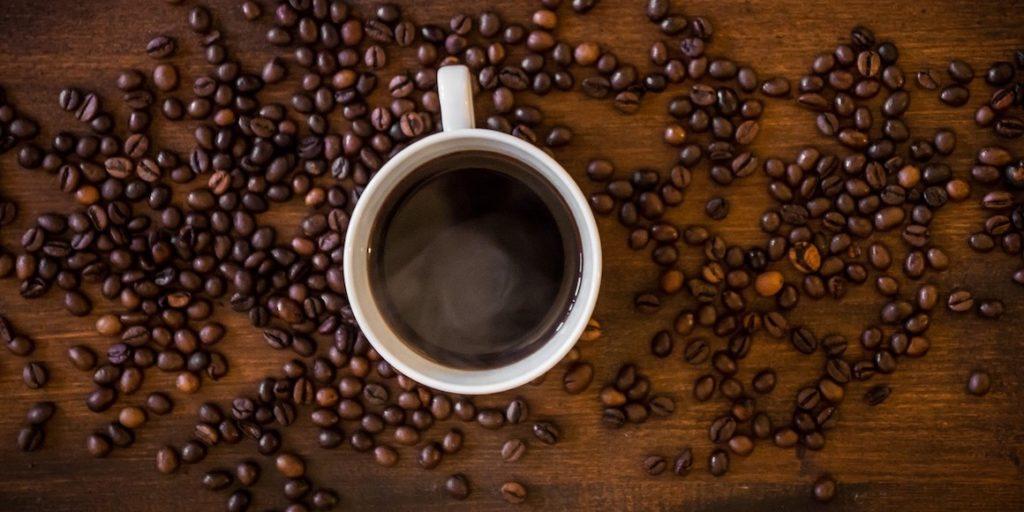 Kopje koffie omringd met koffiebonen
