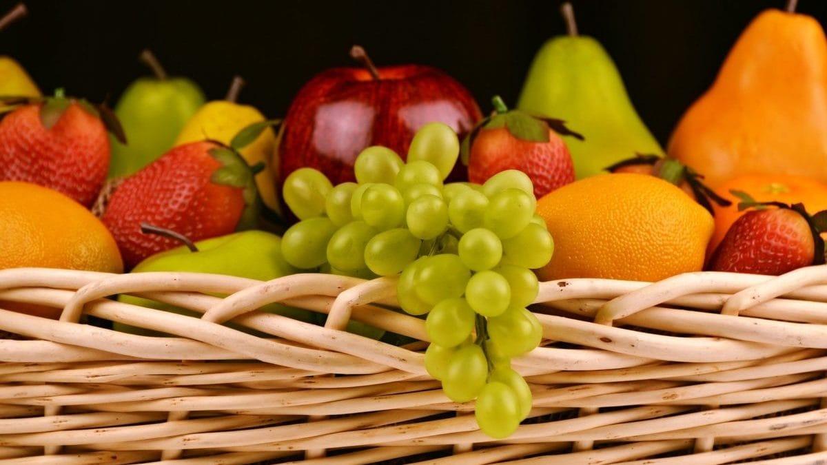 Fruitmand met druiven, appels, peren en aardbeien