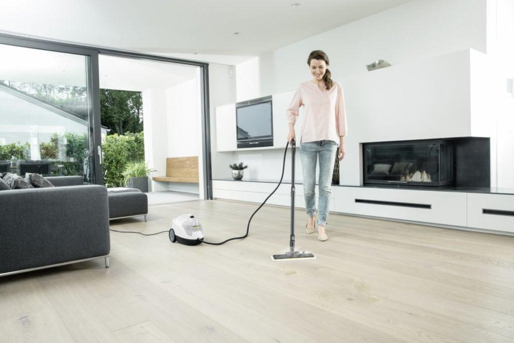 Vrouw die vloer aan het stoom reinigen is