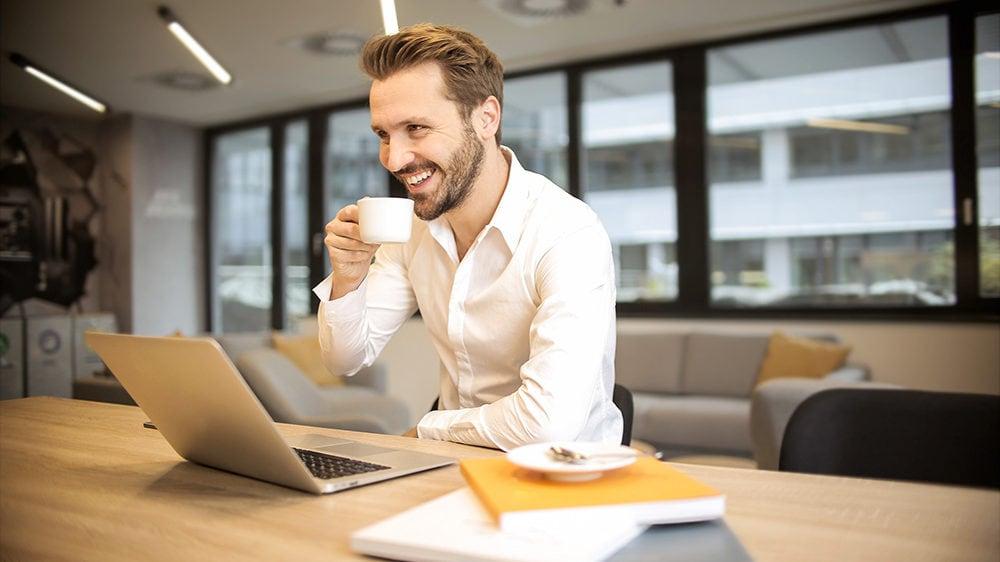 Man aan bureau met koffie en laptop
