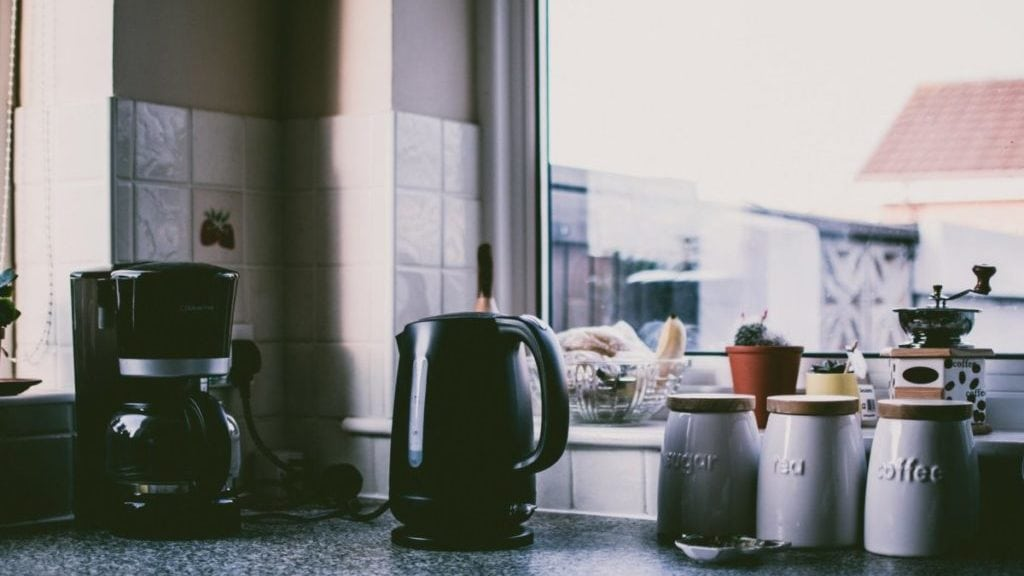 Koffiepot en waterkoker op aanrecht bij raam