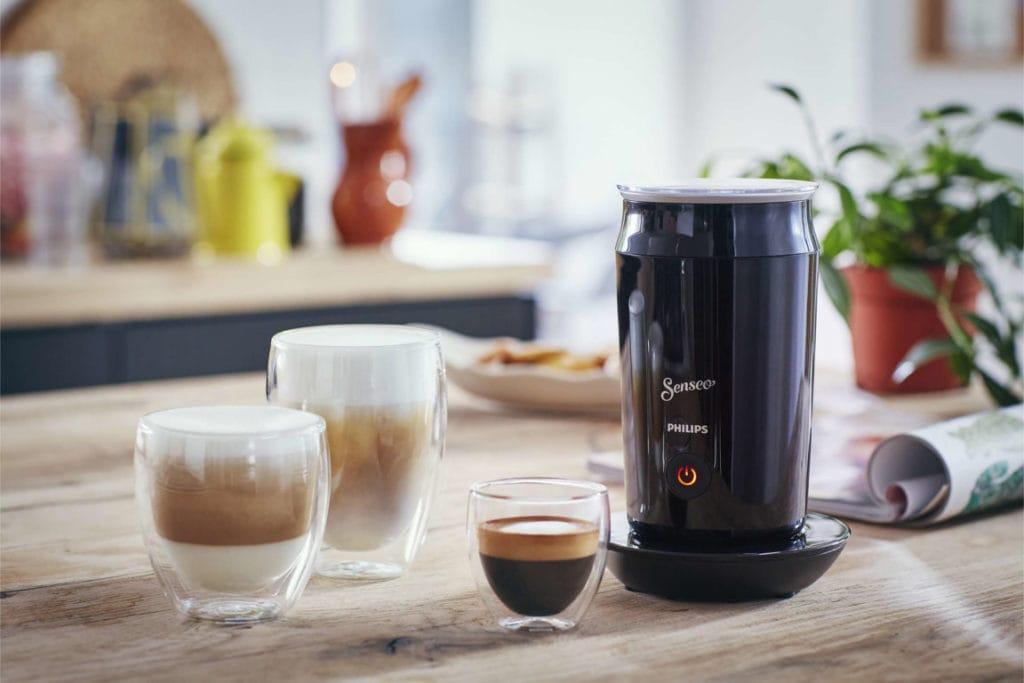 Melkopschuimer met koffiedranken ernaast