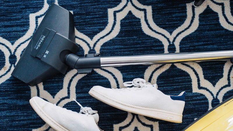 Stofzuiger en witte schoenen op blauw tapijt