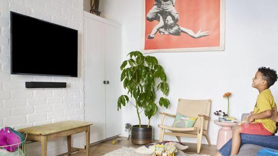 Huiskamer, tv aan de muur en kindje op schoot