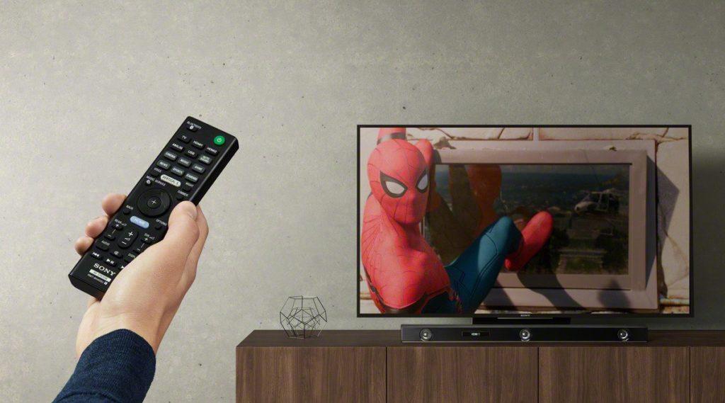 Spiderman op tv, afstandbediening in hand op de voorgrond