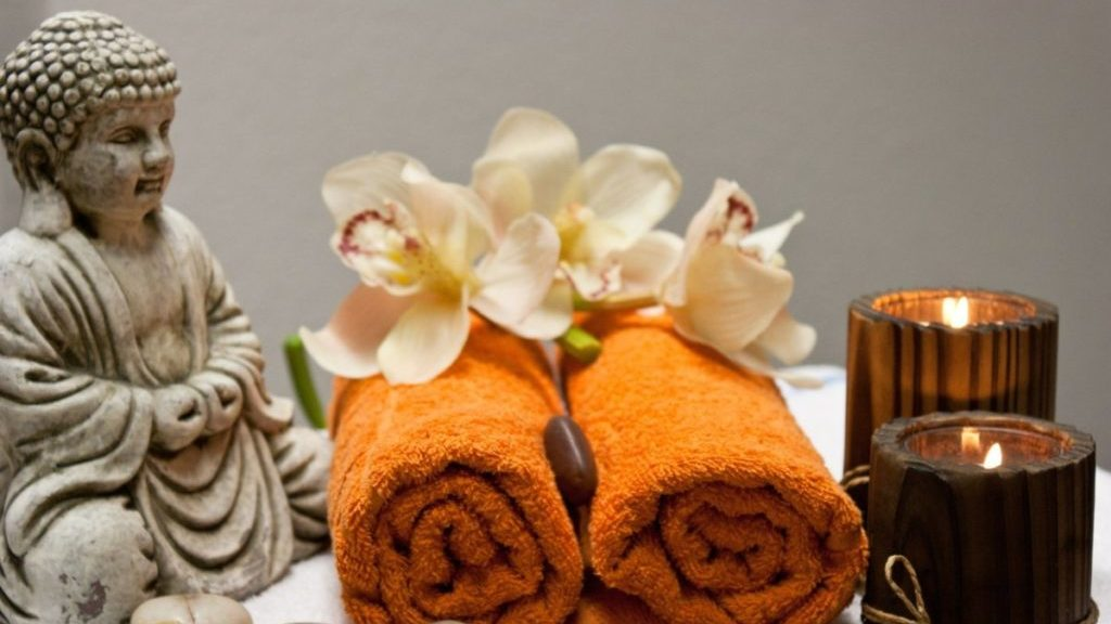 Twee opgerolde oranje handdoeken met buddhabeeldje en twee kaarsjes