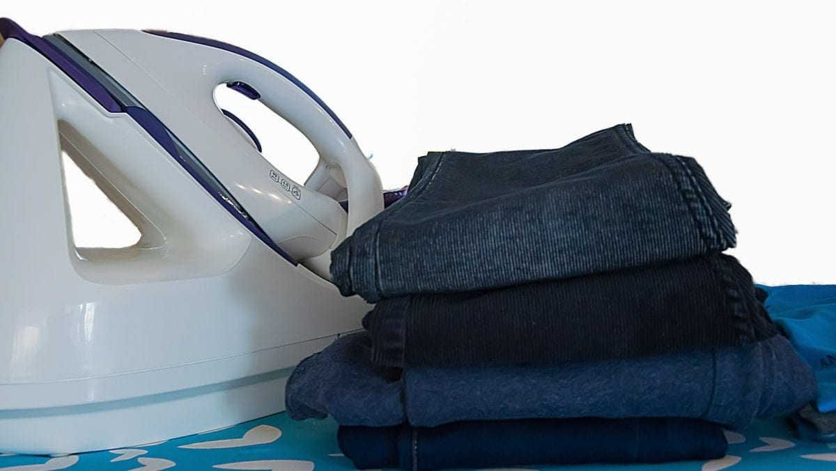 Strijkijzer naast stapel kleding