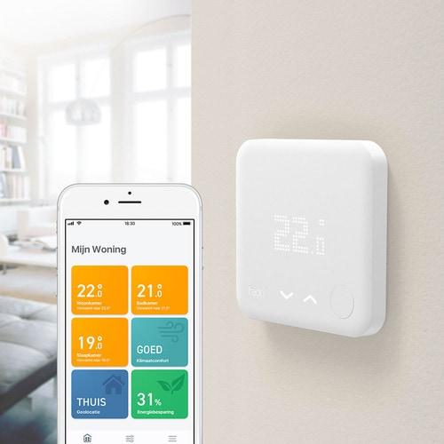 Thermostaat aan de muur met smartphone ernaast