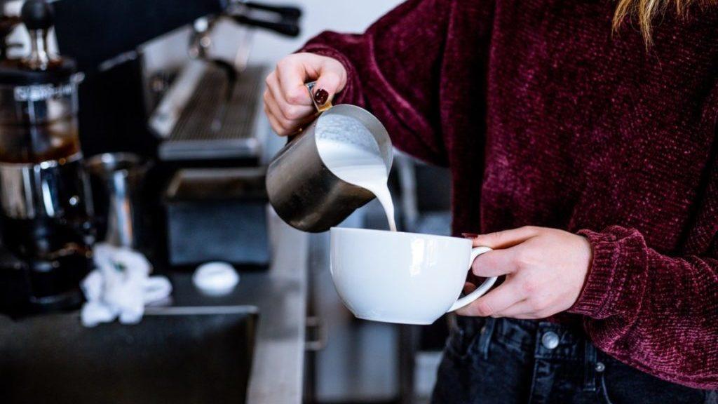 Vrouw schenkt melk in kopje uit kannetje