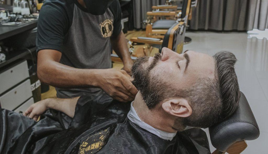 Baard wordt geschoren bij barbier