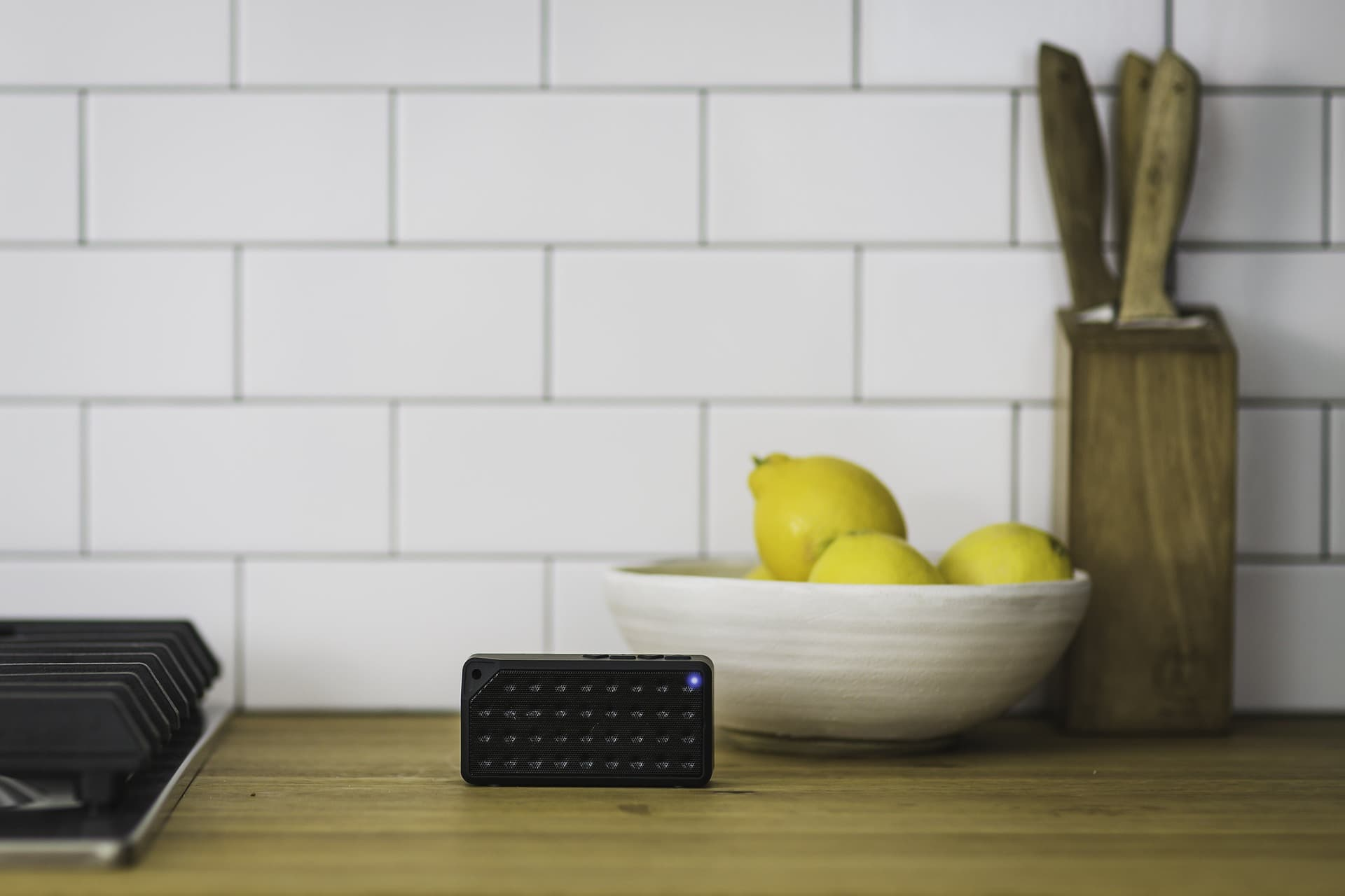 Bluetooth speaker in keuken, bij fruitschaal met citroenen. Vooraanzicht.