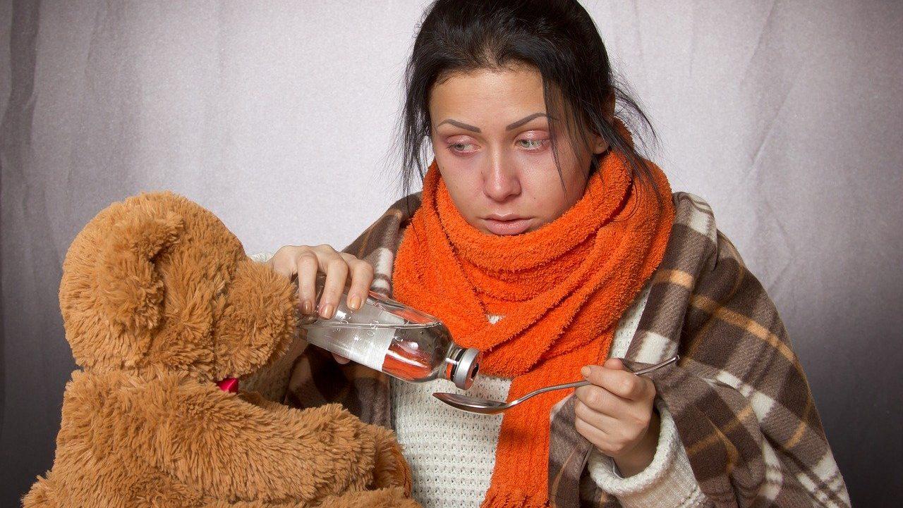 Ziek uitziende persoon met teddybeer en medicijn