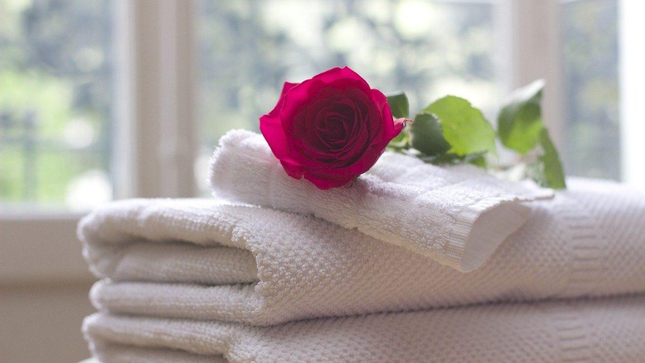 Witte handdoeken met rode roos erop, vooraanzicht