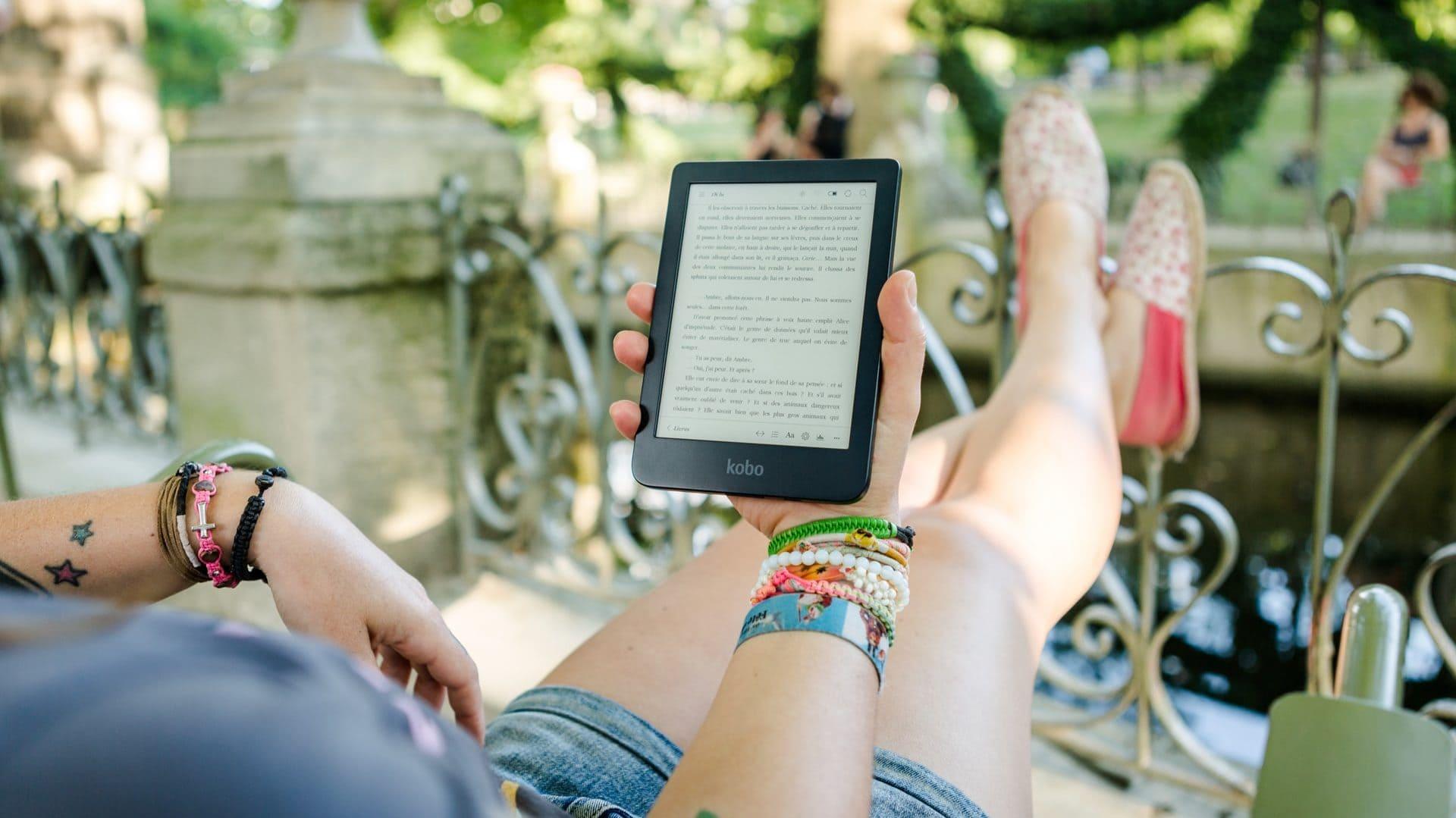 Iemand die in de tuin een e-book leest