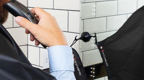 Remington in gebruik boven kapkleed voor spiegel