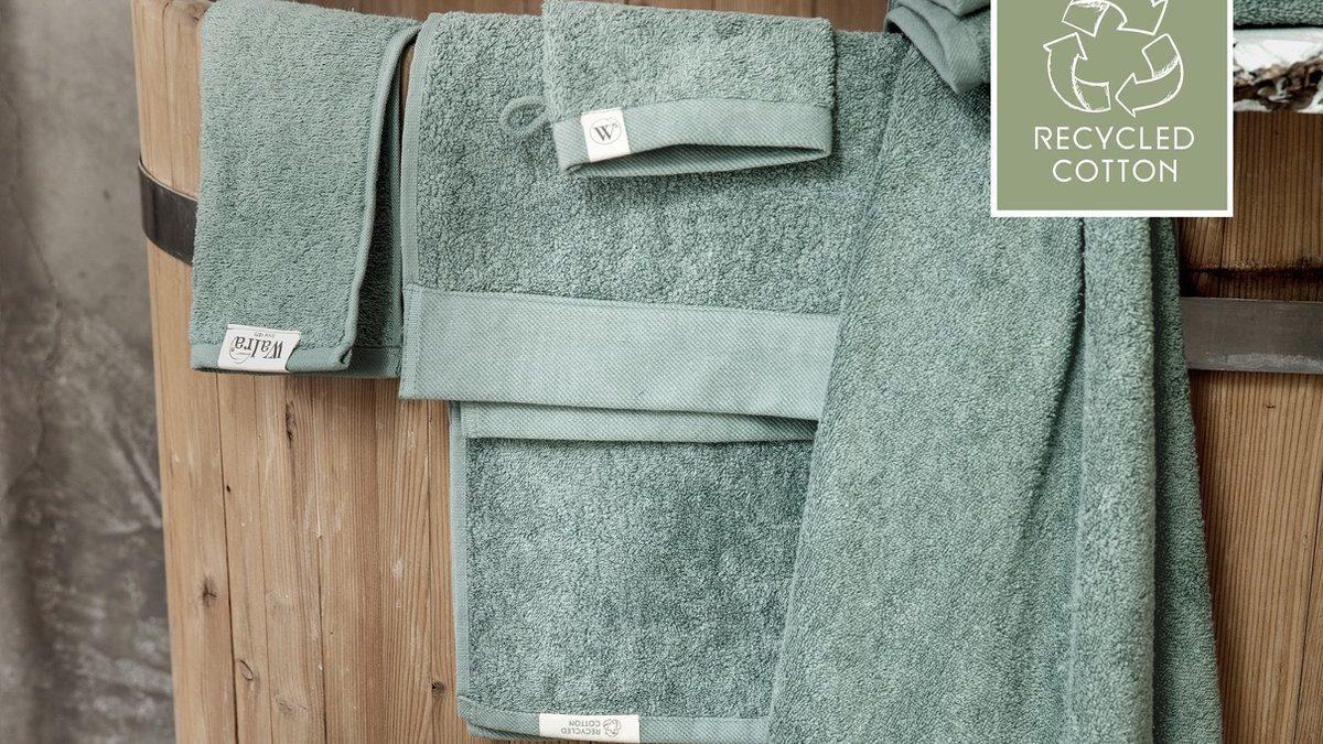 Walra handdoeken die over een houten ton hangen