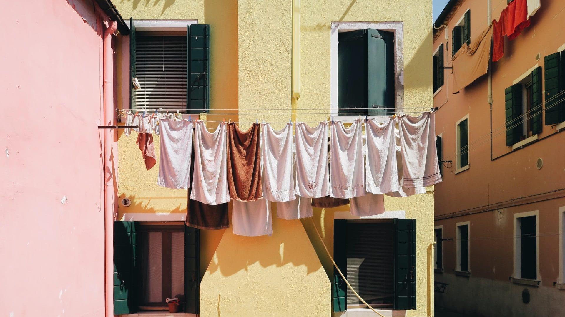 Handdoeken aan de drooglijn tussen kleurrijke gebouwen