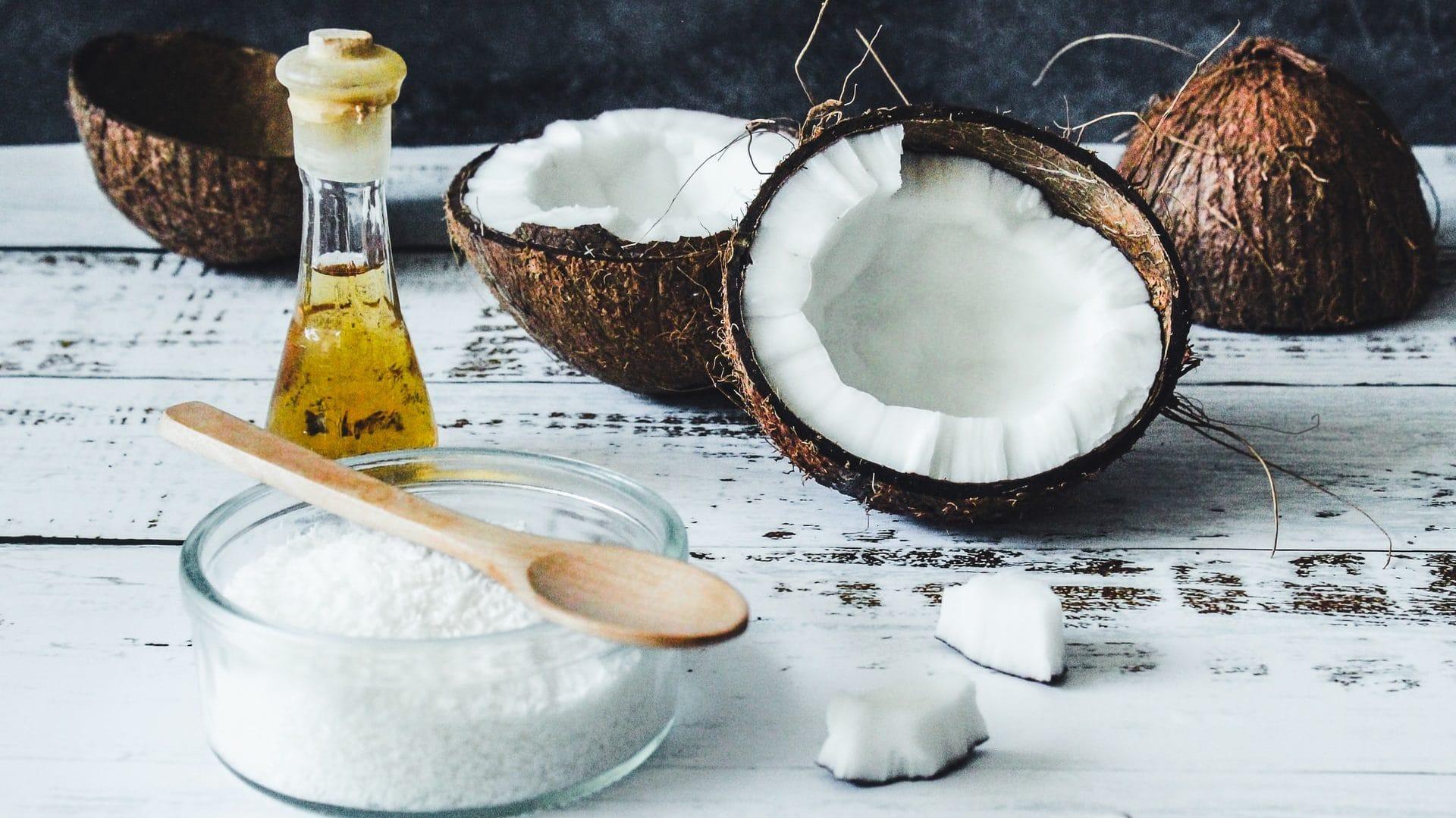 Kokosnoot, zout, lepel en olie op witte ondergrond