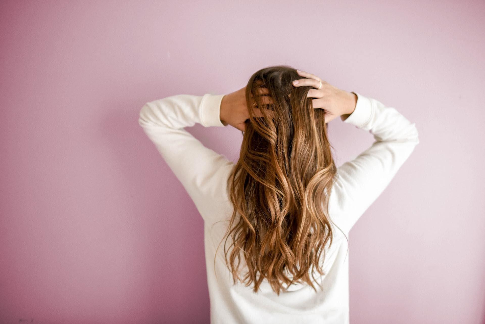 Persoon met lang haar op roze achtergrond