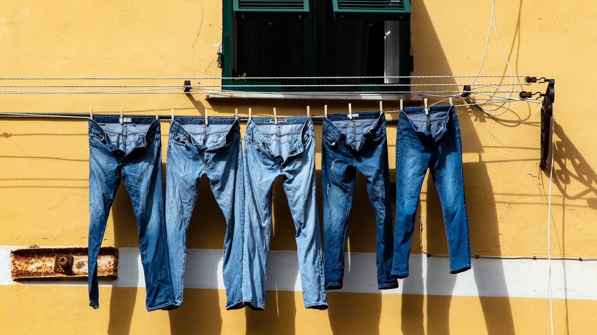 Spijkerbroeken aan de waslijn, gele achtergrond. Vooraanzicht.