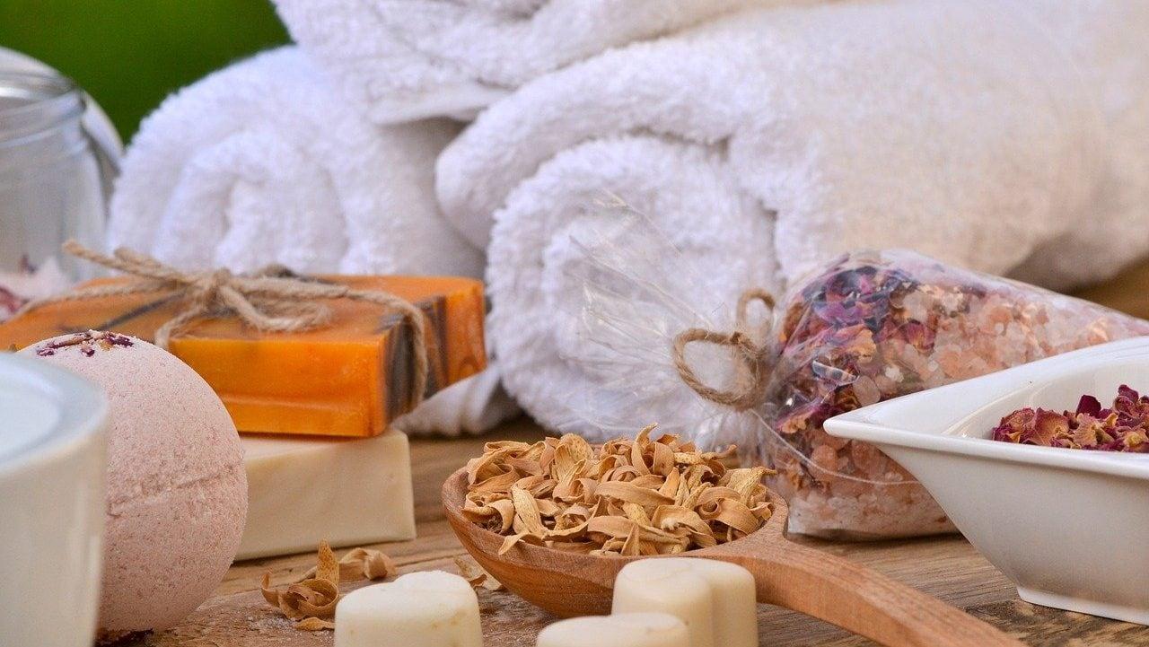 Witte opgerolde handdoeken met zeep en kruiden