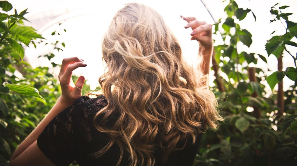 Vrouw met blonde krullen in veld