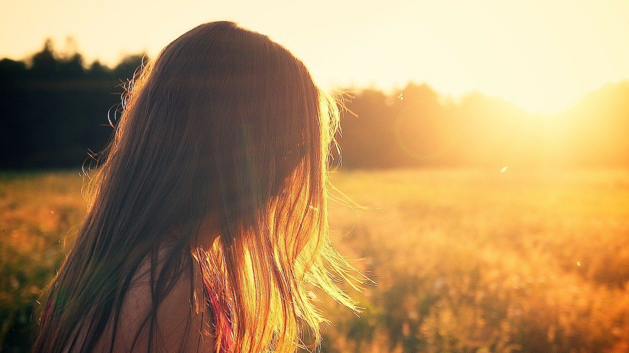 Persoon met lang haar bij zonsondergang