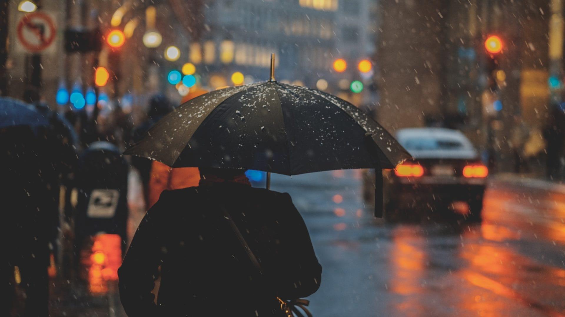 Persoon met paraplu, op straat, achteraanzicht