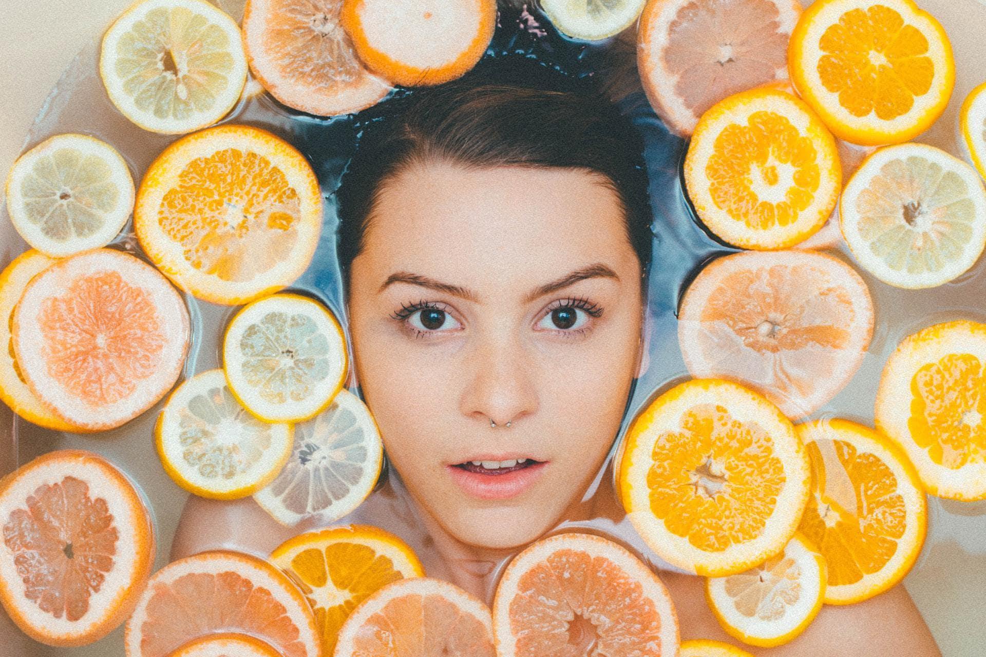 Vrouw in het midden van drijvende sinaasappelschijfjes, bovenaanzicht