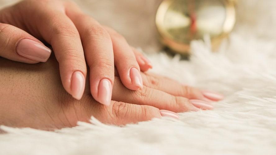 gelakte nagels van handen die over elkaar liggen