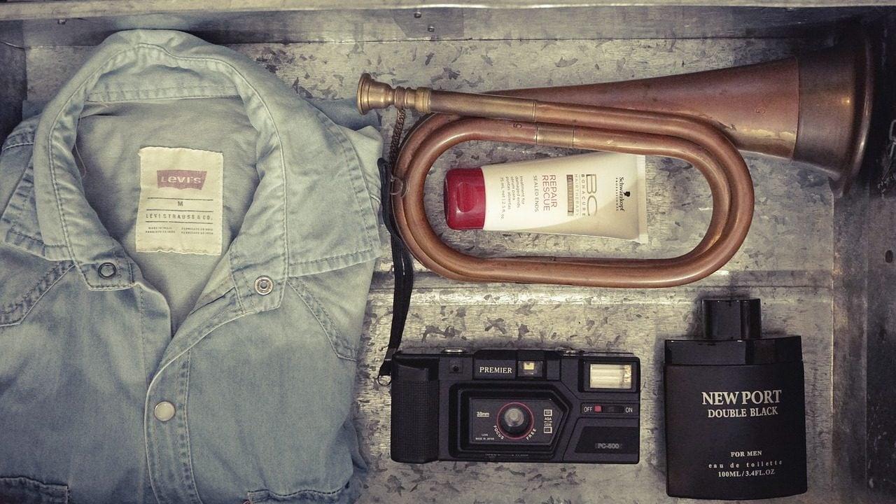 Blouse, muziekinstrument, tube, fototoestel en parfum in kist, bovenaanzicht