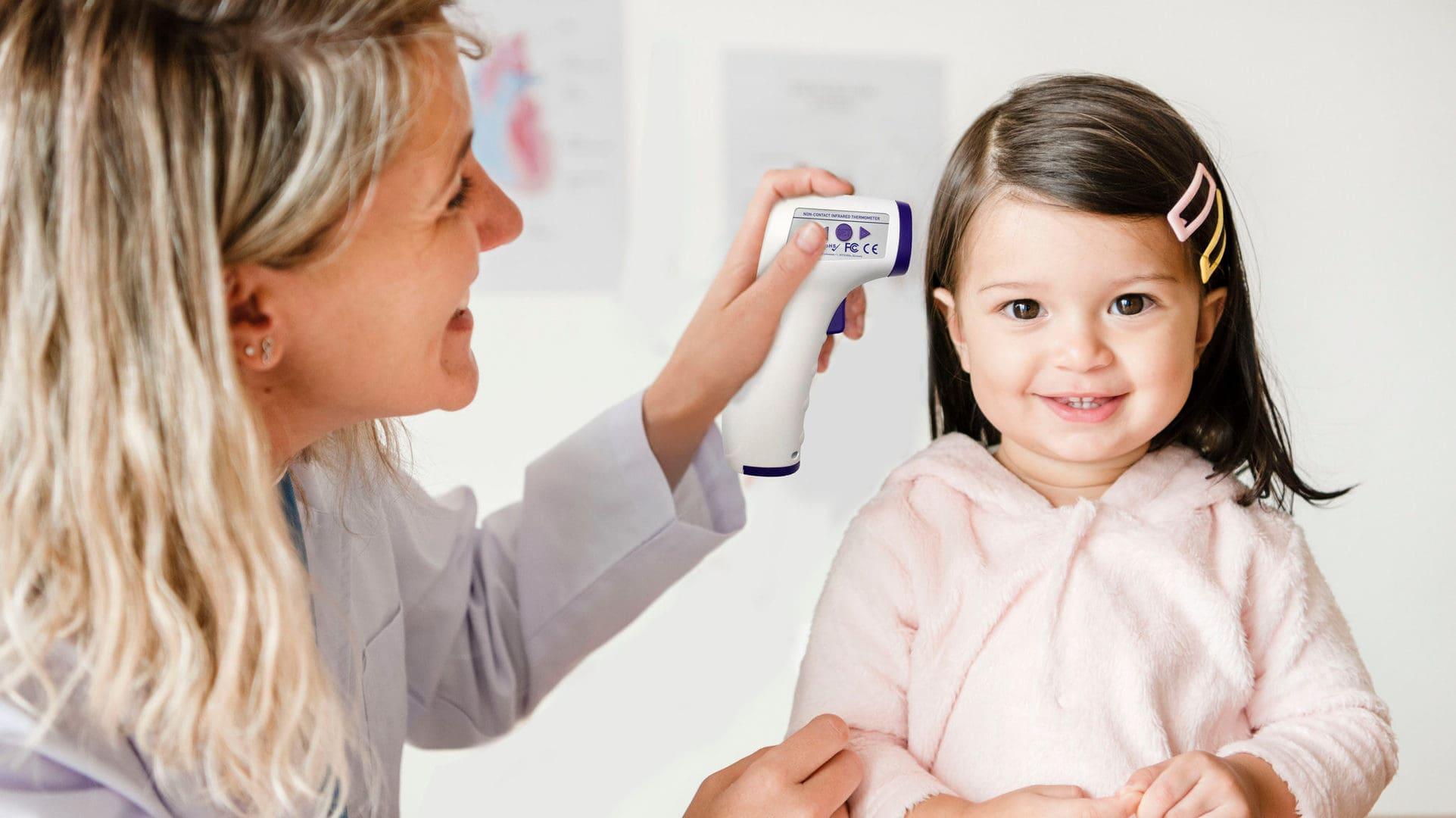 Lachende peuter met moeder die koorts meet