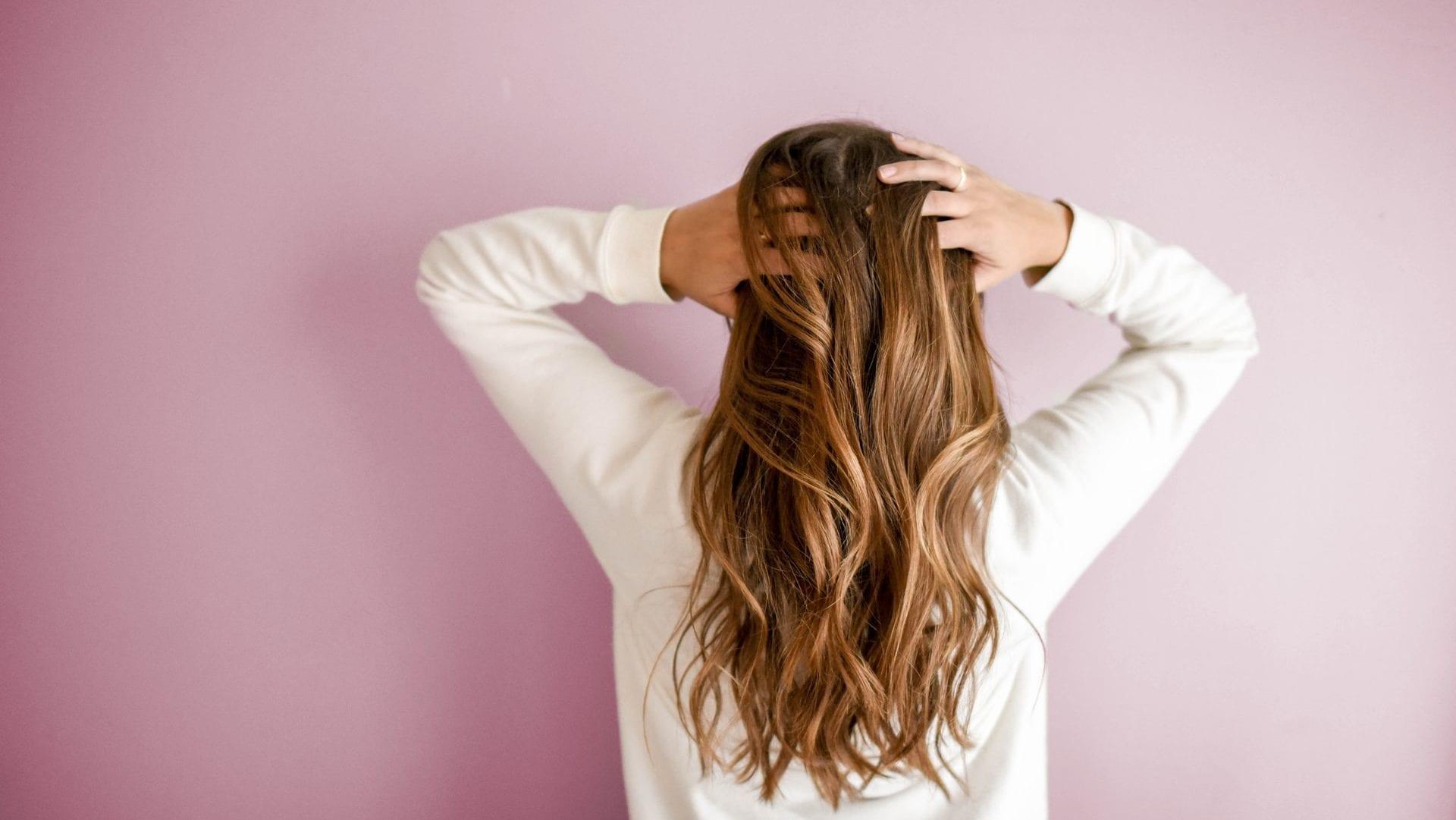 Persoon met lang haar, op roze achtergrond, achteraanzicht