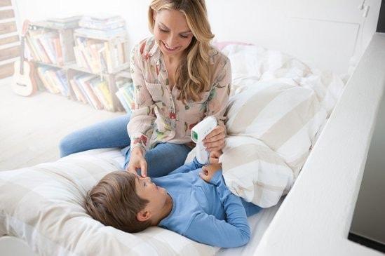 Vrouw met kind en voorhoofdthermometer