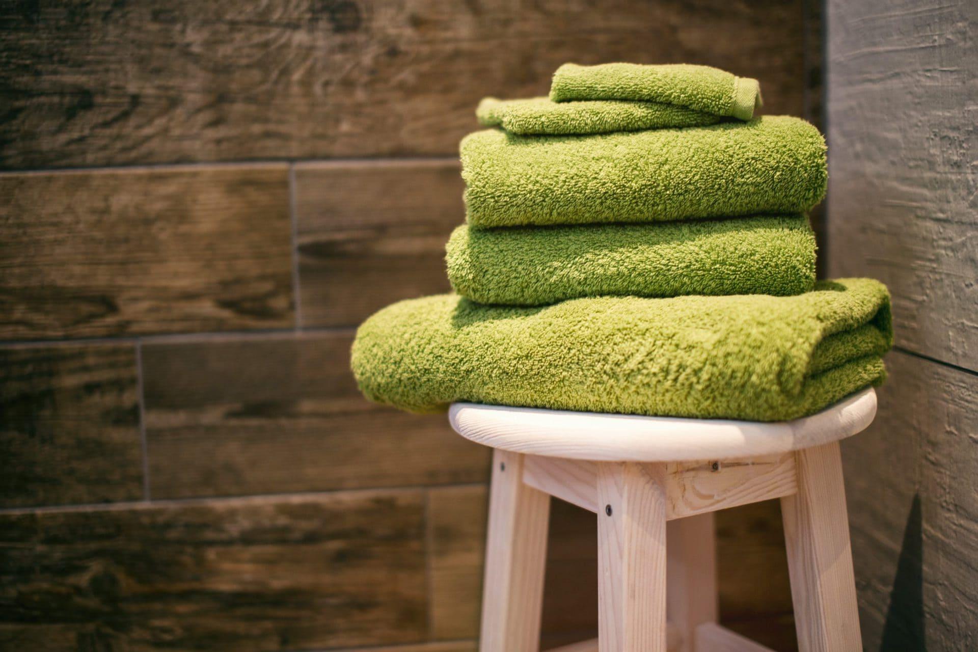 Stapel groene handdoeken op krukje, vooraanzicht