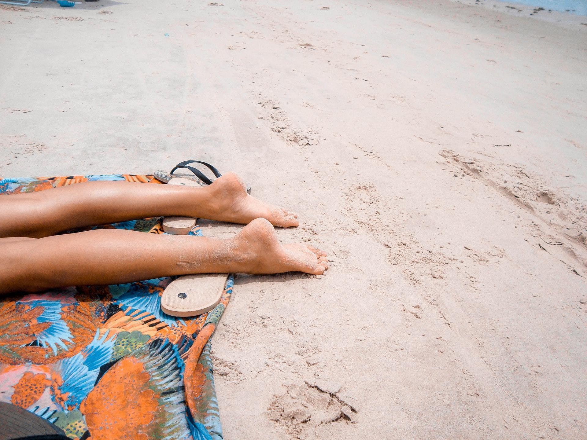 Benen op een zandstrand