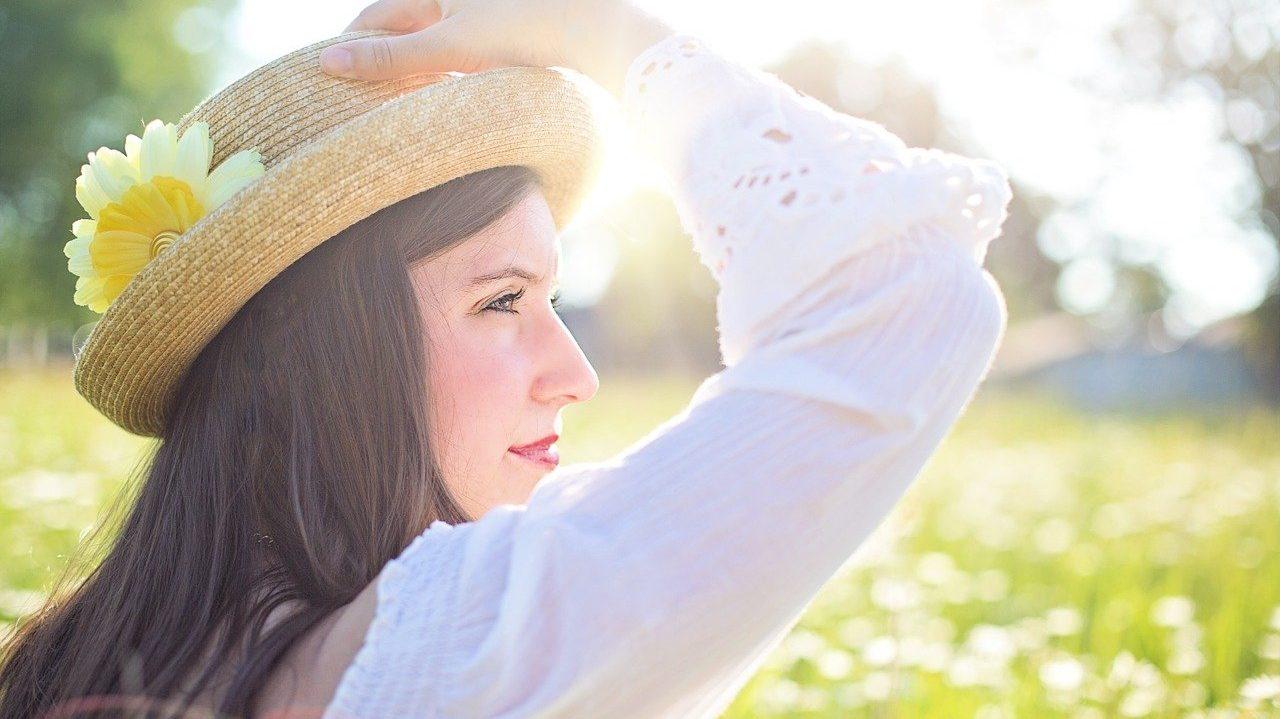 Vrouw met hoed in de zon, zij-aanzicht