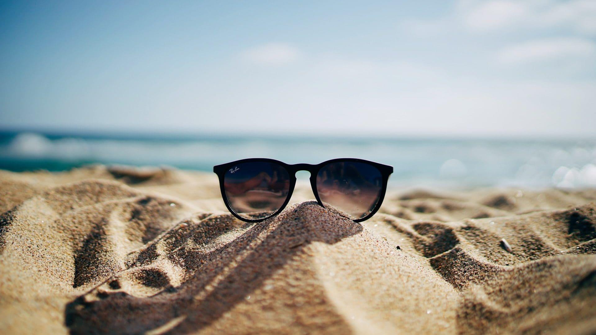Zonnebril op zand voor de oceaan