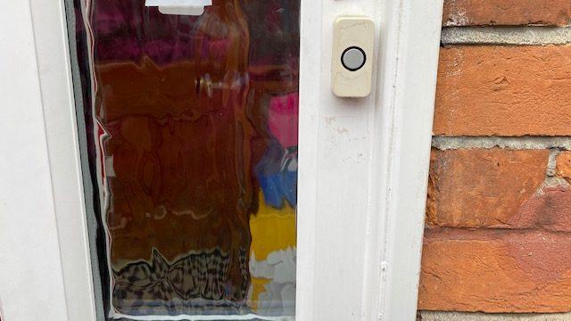 Deurbel aan het kozijn van een voordeur, vooraanzicht